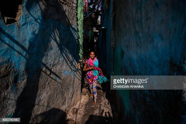 A young Indian girl runs down an alley in the Kathputli Colony in New Delhi on December 20 2016 The name Kathputli Colony comes from the Hindi word...
