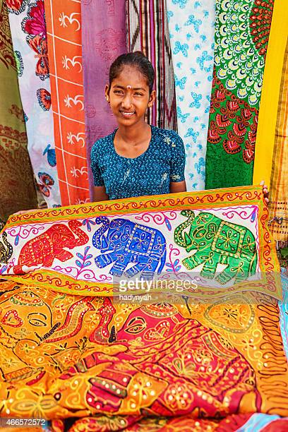Young Indian girl selling colorful embroidered rugs