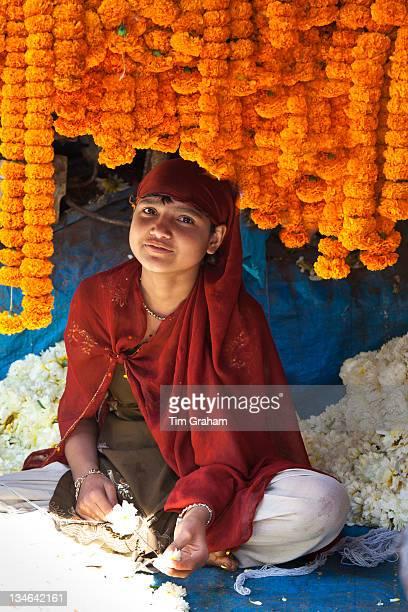 Young Indian girl stringing marigolds in ceremonial Brahmin garlands at Mehrauli Flower Market New Delhi India
