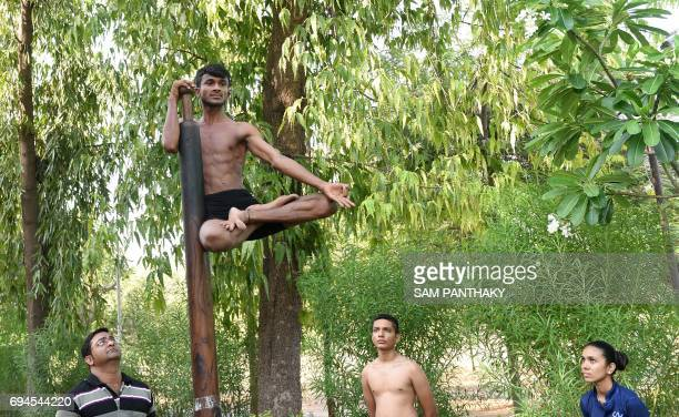 A young Indian gymnast is watched by fellow students as he takes part in a Mallakhamb practice session at CN Sports Academy in Ahmedabad on June 10...
