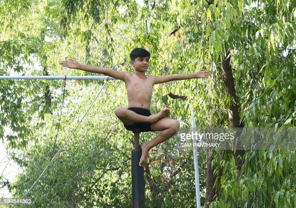 A young Indian gymnast takes part in a Mallakhamb practice session at CN Sports Academy in Ahmedabad on June 10 ahead of the forthcoming Annual Rath...