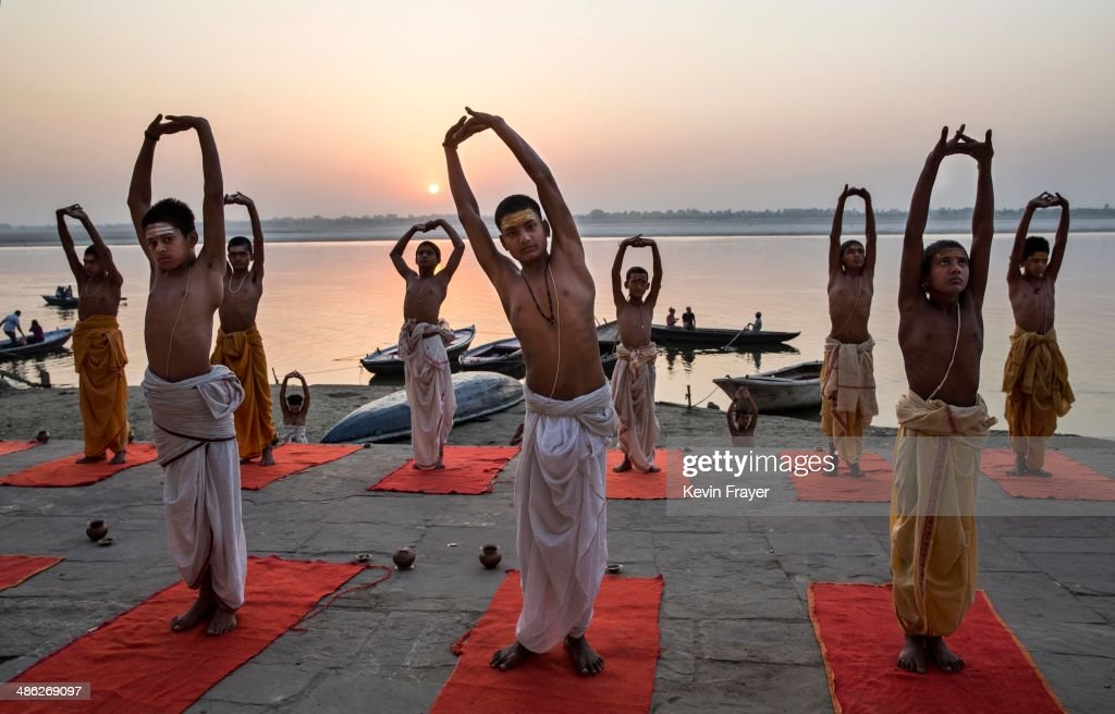 Young Indian Hindu Brahmins training to be priests perform yoga on a ghat on the Ganges River, holy to Hindus, at sunrise on April 23, 2014 in Varanasi, India.