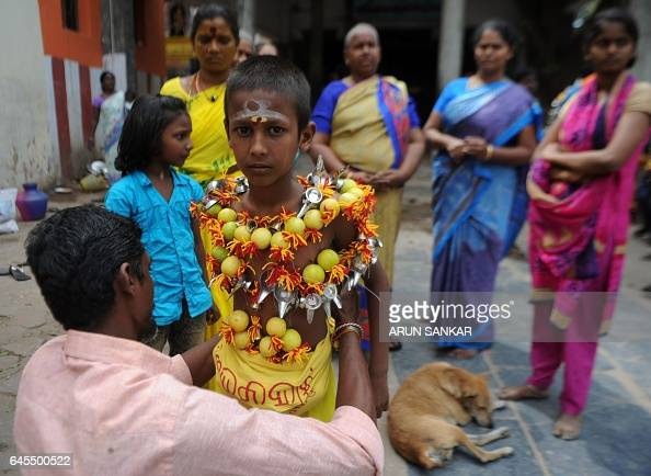 A young Indian Hindu devotee his body pierced with lemon and paladai bowl with a spout mainly used to feed milk to infants prepares to participate in...