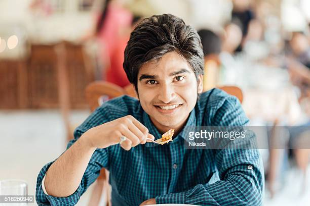 Young Indian Male eating in Restaurant