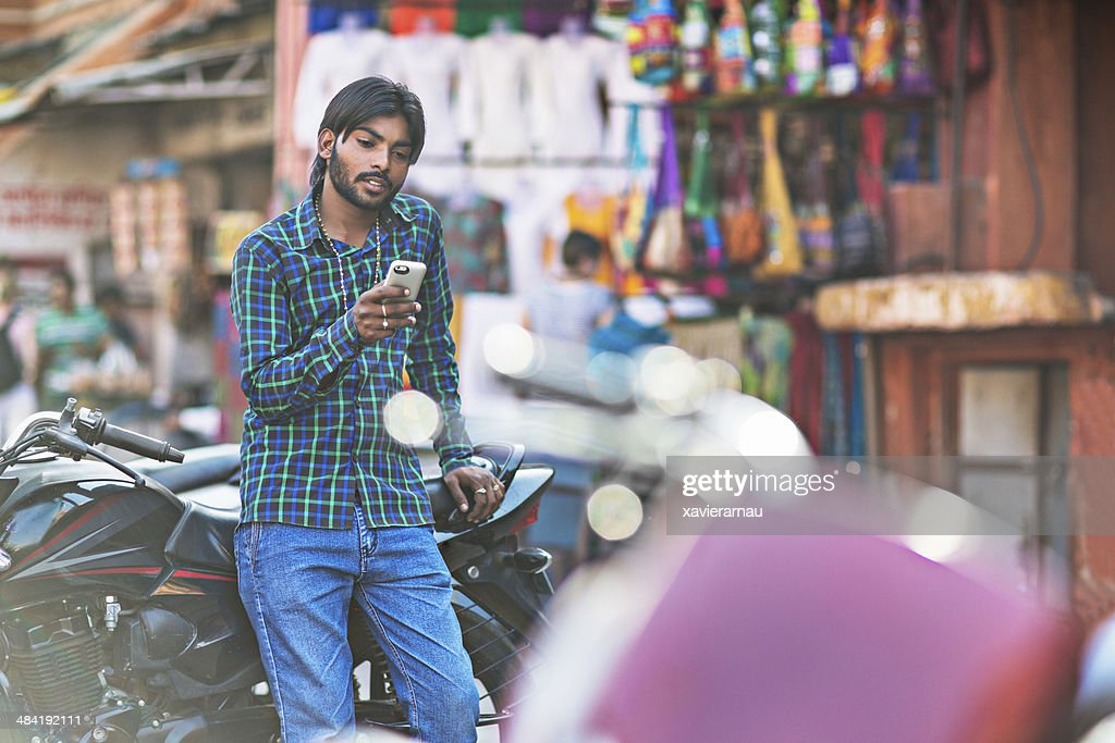 Young indian man typing a message