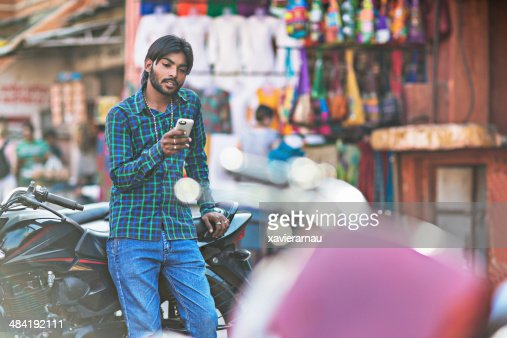 Young Indian man holding phone, with motorbike