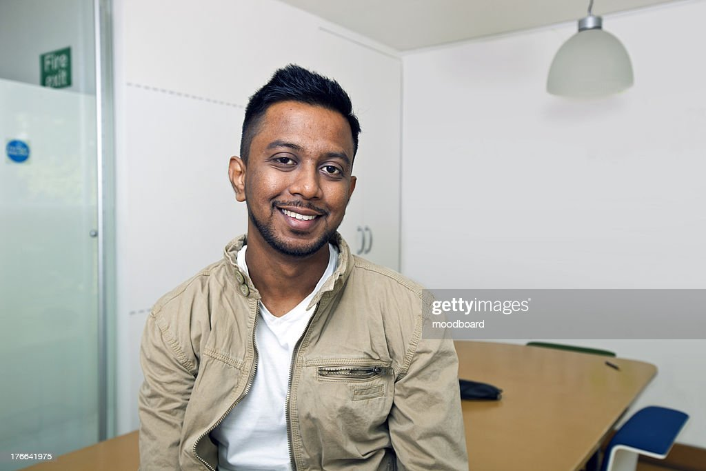Young Indian man smiling at camera in his office : Stock Photo