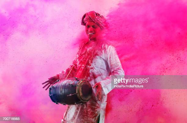 Young Indian man With Colored Face Dancing During Holi Color festival