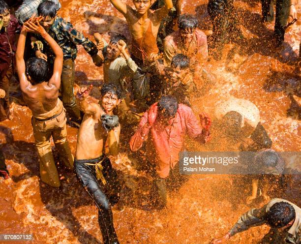 Young Indian men dances inside a temple covered with red dye and water as part of Holi celebrations March 23 2008 in Dugi India Holi is celebrated...