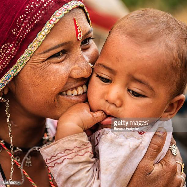 Young Indian mother holding her little baby, village near Jodhpur