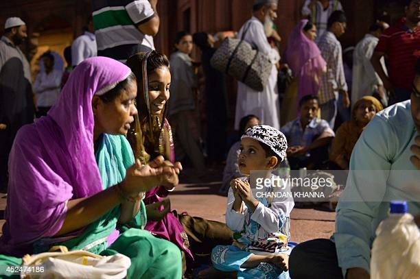 A young Indian muslim boy is taught by relatives to offer namaz during the Islamic holy month of Ramadan in New Delhi on July 20 2014 During the holy...