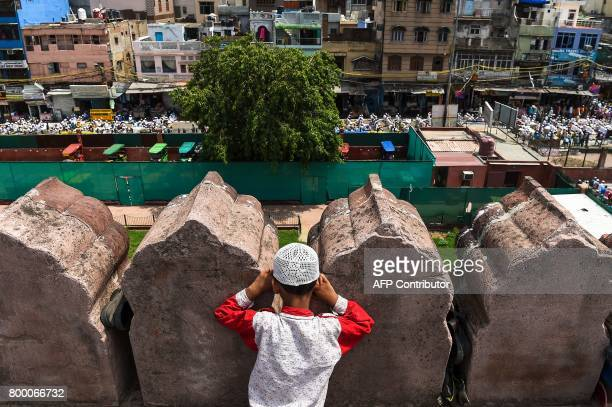 A young Indian Muslim boy looks on as people offer prayers on the last Friday of the holy month of Ramadan at the Jama Masjid mosque ahead of the...