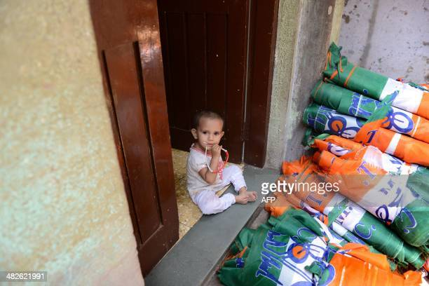 A young Indian Muslim child sits alongside bundles of canvassing material with the logo of the Trinamool Congress Party for the forthcoming elections...