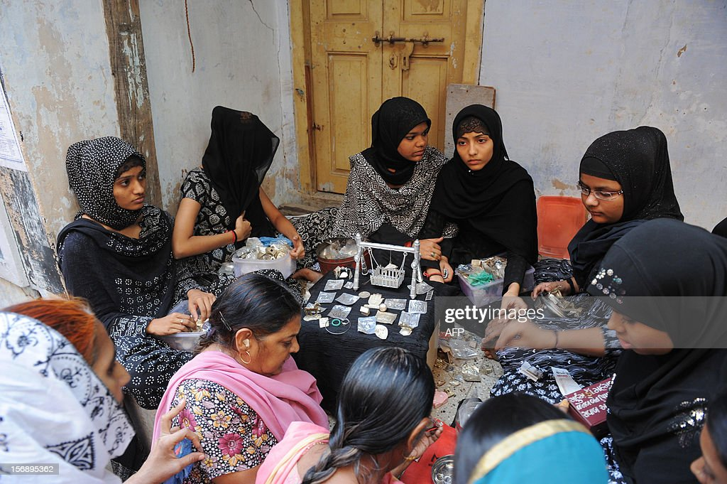 Young Indian Muslim girls pack items of 'Mannat' or wishes for the devotees in Jamalpur area of Ahmedabad during a religious ritual held on the ninth day of Ashura on November 24, 2012. During the Shiite Muslim holy month of Moharram, large processions are formed and the devotees parade the streets holding banners and carrying models of the mausoleum of Hazrat Imam Hussain and his people, who fell at Karbala. Shias show their grief and sorrow by inflicting wounds on their own bodies with sharp metal tied to chains to depict the sufferings of the martyrs. AFP PHOTO / Sam PANTHAKY