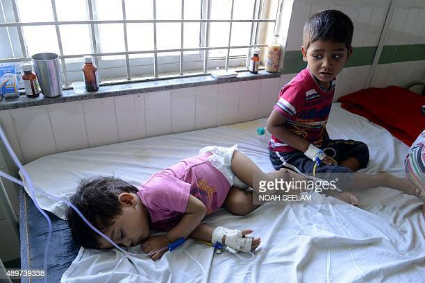 Young Indian patients sit on a bed as they are treated on a swine flu ward at The Gandhi Hospital in Hyderabad on September 24 2015 Five positive...