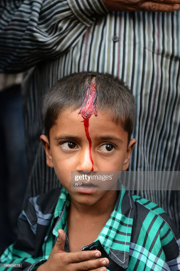 A young Indian Shiite Muslim devotee prays afterperforming ritual acts of self flagelation with a cluster of knives and chains during a religious procession in Ahmedabad on November 22, 2012. Rituals are held on the seventh day of Moharram, which commemorates the seventh century slaying of the Prophet Mohammed's grandson in southern Iraq. During the holy month of Muharram, large processions are formed and the devotees parade the streets holding banners and carrying models of the mausoleum of Hazrat Imam Hussain and his people, who fell at Karbala. Muslims show their grief and sorrow by inflicting wounds on their own bodies with sharp metal tied to chain with which they scourge themselves, in order to depict the sufferings of the martyrs AFP PHOTO / Sam PANTHAKY