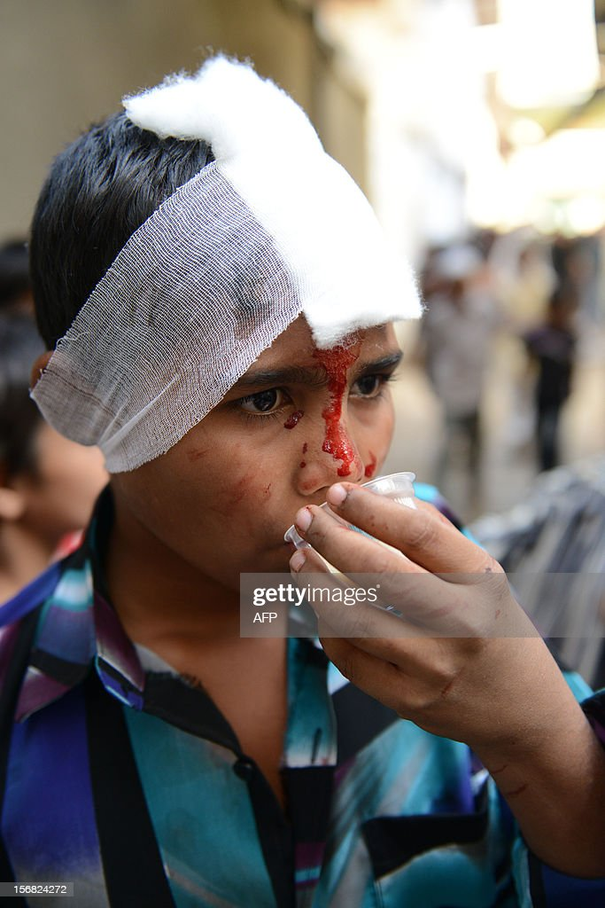 A young Indian Shiite Muslim devotee sips a cup of coffee after performing ritual acts of self flagelation with a cluster of knives and chains during a religious procession in Ahmedabad on November 22, 2012. Rituals are held on the seventh day of Moharram, which commemorates the seventh century slaying of the Prophet Mohammed's grandson in southern Iraq. During the holy month of Muharram, large processions are formed and the devotees parade the streets holding banners and carrying models of the mausoleum of Hazrat Imam Hussain and his people, who fell at Karbala. Muslims show their grief and sorrow by inflicting wounds on their own bodies with sharp metal tied to chain with which they scourge themselves, in order to depict the sufferings of the martyrs AFP PHOTO / Sam PANTHAKY