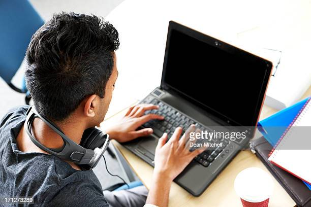 Young Indian student using laptop computer