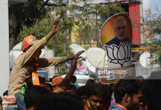 A young Indian supporter of Bhartiya Janta Party celebrates after election results outside the party state head quarter in Lucknow capital and...