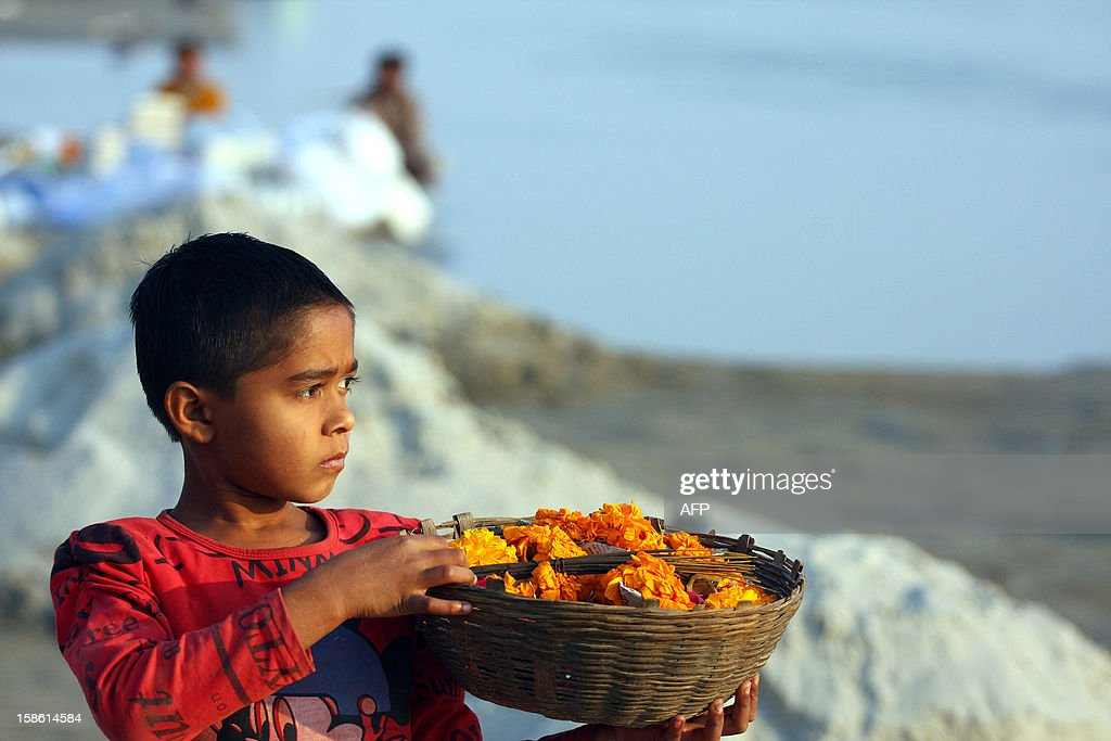 """A young Indian vendor walks with a basket of marigolds on the banks of """"Sangam,"""" the confluence of the three rivers Ganges, Yamuna and mythical Saraswati in Allahabad on December 21, 2012. The Kumbh Mela, which is scheduled to take place in the northern Indian city in January and February 2013, is the world's largest gathering of people for a religious purpose and millions of people gather for this auspicious occasion. AFP PHOTO/ Sanjay KANOJIA"""