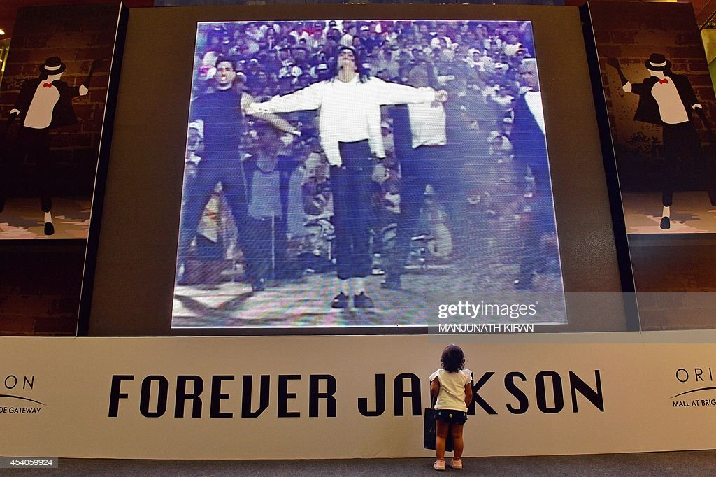 A young Indian visitors watches a music video of the late US pop star Michael Jackson at a commemorative exhibition, set up at the mall as part of birthday celebrations for the late music icon, in Bangalore on August 23, 2014. Fans of the lengendary pop star Michael Jackson, who passed away in 2009, are gearing up to celebrate what would have been his 56th birthday on August 29. AFP PHOTO/Manjunath KIRAN