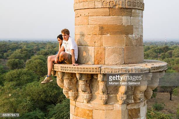 Young Indian woman and caucasian man sitting p top one of the two minarets of the abandoned Kevda Masjid Mosque in Champagner Gujarat
