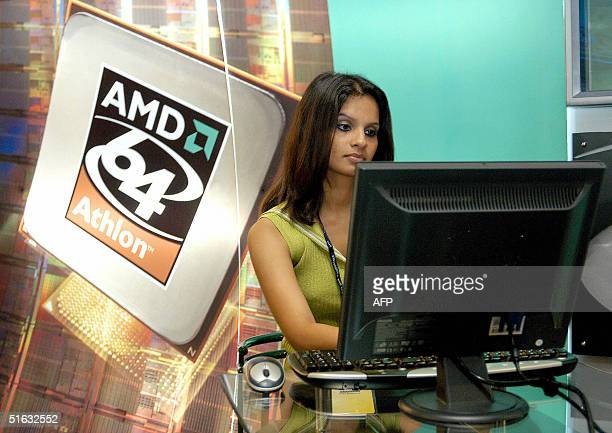 A young Indian woman checks out the performance of an AMD Athlon 64bit processor based PC at the AMD stall at the 7th Edition of the Annual...