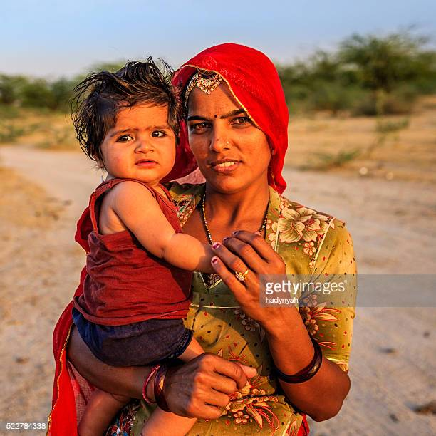 Young Indian woman holding her little baby, India