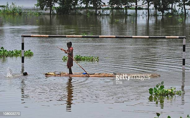 A young Indian woman paddles a banana raft past a partially submerged pair of goalposts in the village of Bordiya of Morigoan District some 70kms...