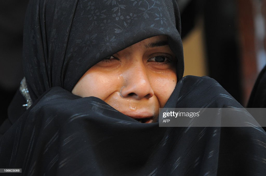 A young Indian woman reacts as Shiite Muslims perform ritual acts of self flagelation with a cluster of knives and chains during a religious procession in Ahmedabad on November 22, 2012. Rituals are held on the seventh day of Moharram, which commemorates the seventh century slaying of the Prophet Mohammed's grandson in southern Iraq. During the holy month of Muharram, large processions are formed and the devotees parade the streets holding banners and carrying models of the mausoleum of Hazrat Imam Hussain and his people, who fell at Karbala. Muslims show their grief and sorrow by inflicting wounds on their own bodies with sharp metal tied to chain with which they scourge themselves, in order to depict the sufferings of the martyrs. AFP PHOTO / Sam PANTHAKY