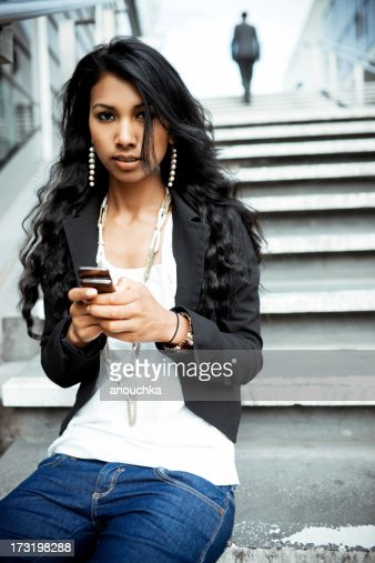 Young Indian Woman sitting on staircase with mobile phone
