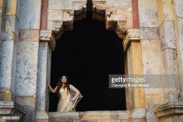 Young Indian Woman Standing at a Big Window of a Historical Monument Shisha Gumbad at Lodhi Gardens with Traditional Ethnic Clothing