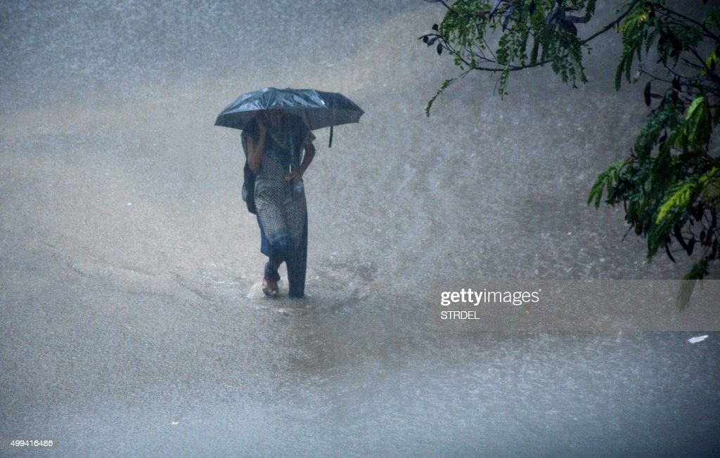 A young Indian woman walks under an umbrella through floodwaters in Chennai on December 1 during a downpour of heavy rain in the southern Indian city...