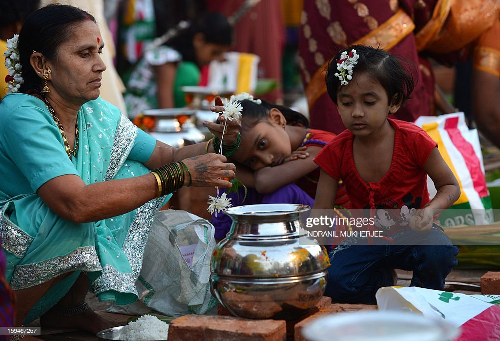 Young Indian's look on as their grandmother performs a ritual at a community function during the Pongal festival in Mumbai on January 14, 2013. Pongal is a thanksgiving or harvest festival celebrated by people hailing from the Indian state of Tamil Nadu. Pongal-which coincides with the Hindu festival Makara Sankranthi and is celebrated throughout India as the winter harvest, is usually held from January 13–16.