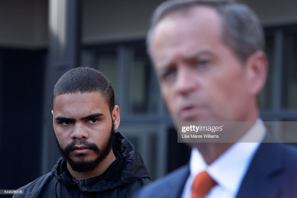 A young indigenous man looks on as Opposition Leader, Australian Labor Party <a gi-track='captionPersonalityLinkClicked' href=/galleries/search?phrase=Bill+Shorten&family=editorial&specificpeople=606712 ng-click='$event.stopPropagation()'>Bill Shorten</a> speaks with the media during a visit to the Tharawal Aboriginal Corporation Child and Family Centre in Campbeltown on July 1, 2016 in Sydney, Australia. <a gi-track='captionPersonalityLinkClicked' href=/galleries/search?phrase=Bill+Shorten&family=editorial&specificpeople=606712 ng-click='$event.stopPropagation()'>Bill Shorten</a> is campaigning heavily on Medicare, promising to make sure it isn't privatised if the Labor Party wins the Federal Election on July 2.