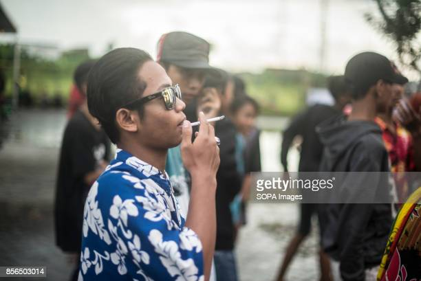 A young Indonesia man smoke a cigaret during a reggae show Music live 'Warkop' is the name of Indonesia small cafeterias where young people drink tea...
