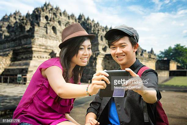 Young Indonesian couple shots selfie in front of Borobudur