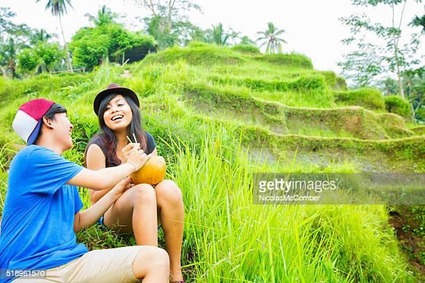 Young Indonesian friends laugh while resting during rice paddy hike
