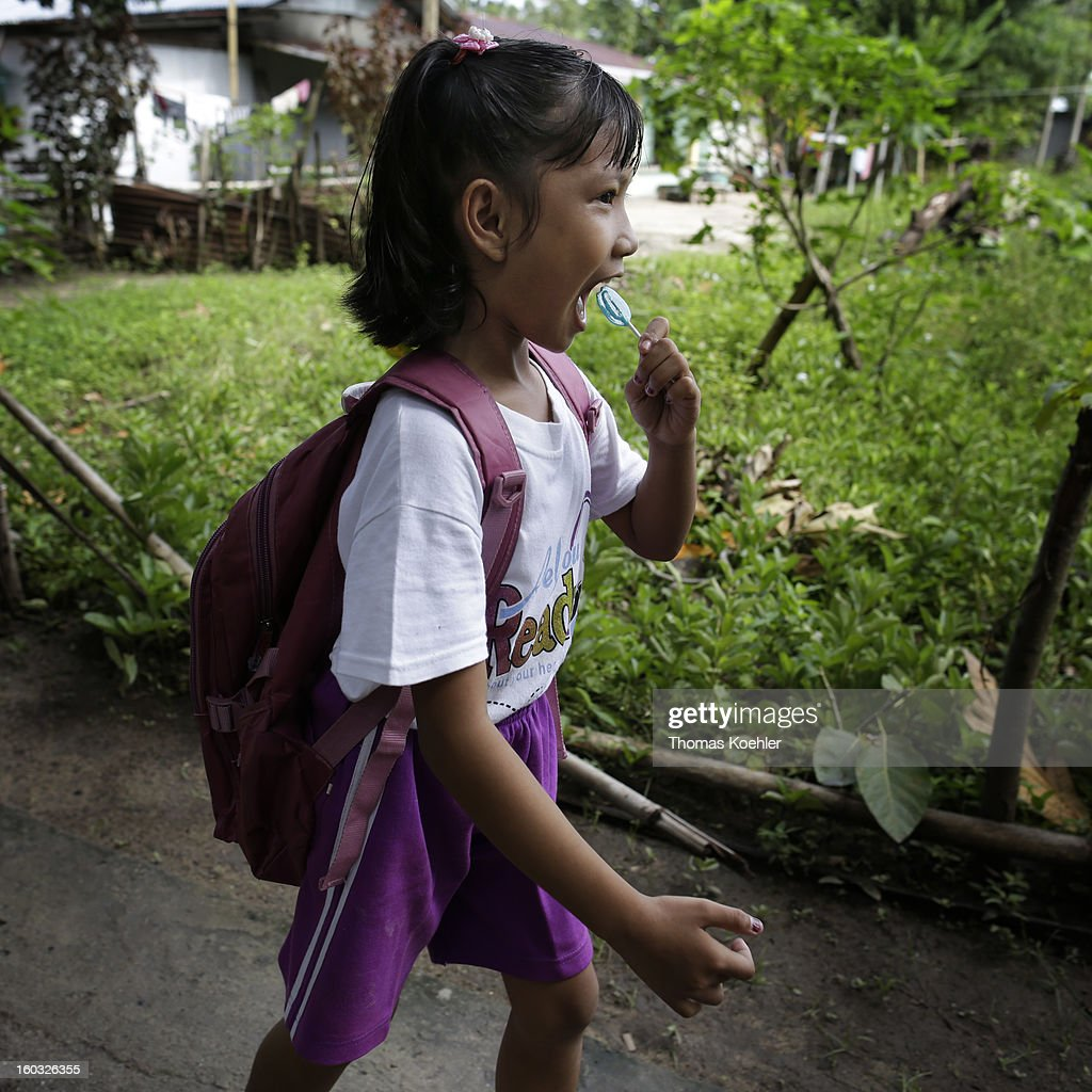 A young Indonesian girl, walking along, eating a lollipop on the island of Bunaken near Manado, Indonesia on January 11, 2013.