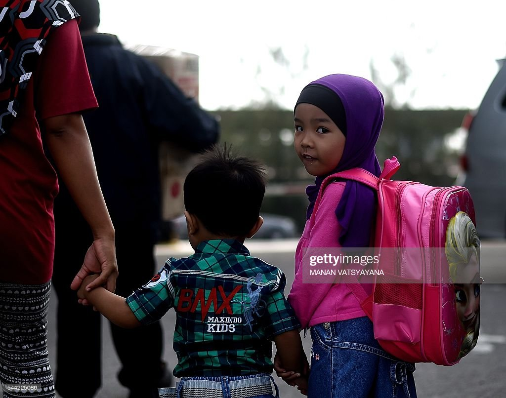 A young Indonesian girl walks with her family to board a ferry to head home ahead of the Eid al-Fitr festival at the port passenger terminal in Port Klang on July 2, 2016. A large number of Indonesians living in Malaysia head back home to celebrate Eid Al-fitr festival with their families during the last days of the fasting month of Ramadan. / AFP / MANAN