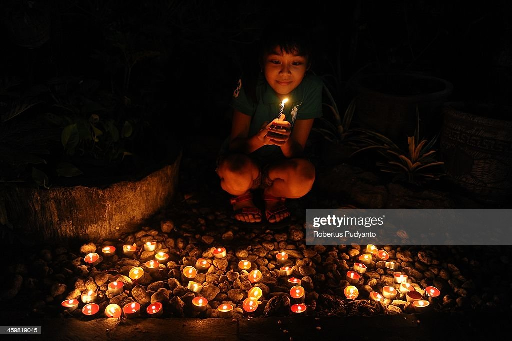 A young Indonesian lites candles and prays to celebrate 2014 New Years on December 31, 2013 in Surabaya, Indonesia. A wave of pyrotechnic displays kicked off New Years celebrations in major cities around the world.