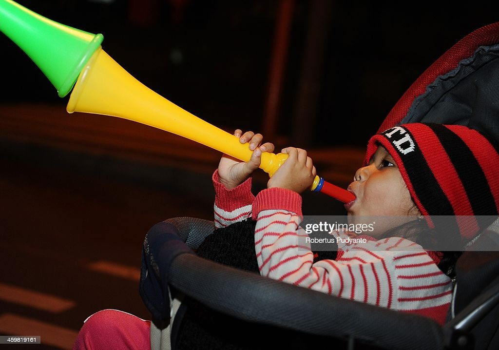 A young Indonesian plays trumpet to celebrate 2014 New Years on December 31, 2013 in Surabaya, Indonesia. A wave of pyrotechnic displays kicked off New Years celebrations in major cities around the world.