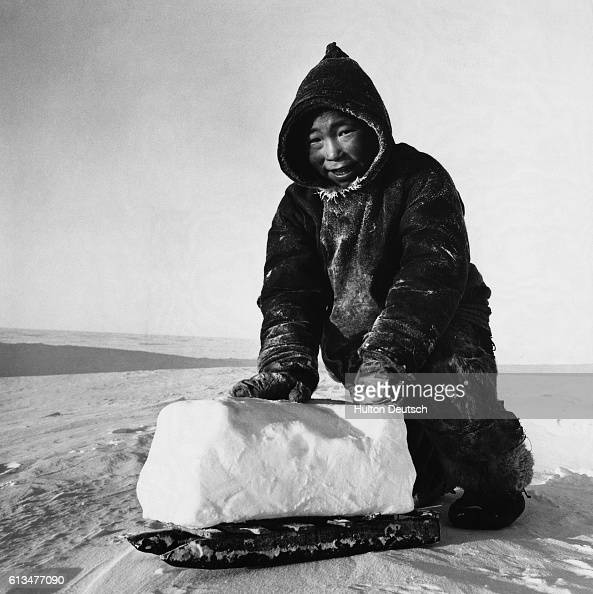 A young inhabitant of the Melville Peninsula uses a small sled to transport a block of frozen snow home to melt for tea
