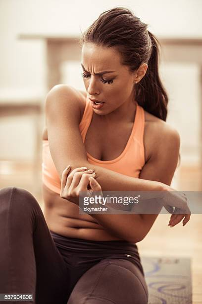 Young injured athletic woman holding her elbow in pain.