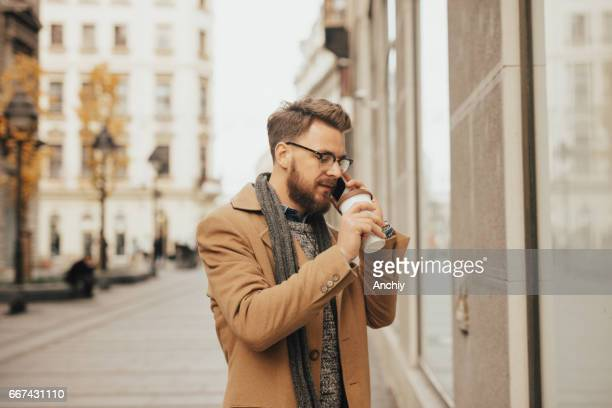 Young intern drinking coffee on the way to work