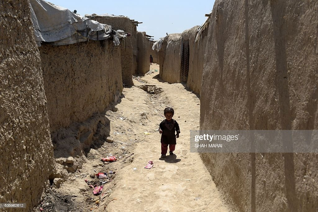 A young Internally-displaced Afghan child walks at a refugee camp in Kabul on May 31, 2016. The number of people internally displaced by war in Afghanistan has doubled since 2012 to 1.2 million, Amnesty International said on May 31, citing government neglect and a lack of international attention. In its report entitled 'My children will die this winter: Afghanistan's broken promise to the displaced', the rights group warned that a lack of basic services had pushed many of those uprooted from their homes to the brink of survival. / AFP / SHAH