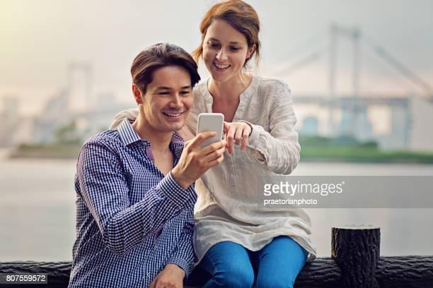 Interracial Pärchen sucht in einem Mobiltelefon an der Vorderseite des Tokyo City und Regenbogen-Brücke