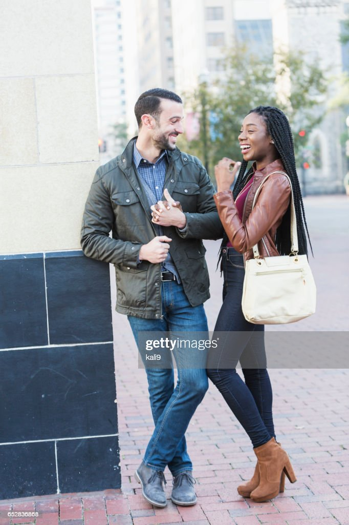 Young interracial couple walking in city : Stock Photo