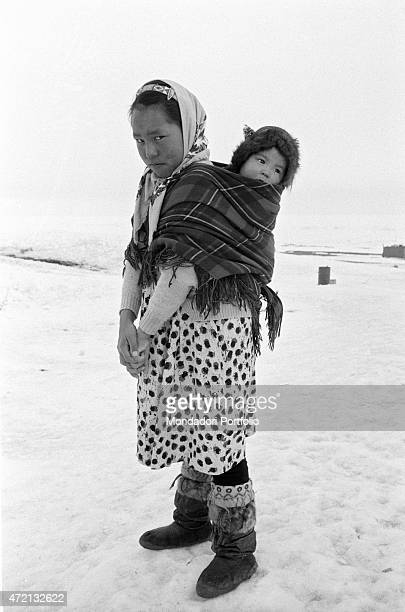 'A young Inuit woman carrying her baby in a scarf tied on her back Resolute 1959 '