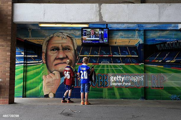 Young Ipswich fans in front of a mural of former Manager Sir Bobby Robson ahead of the Sky Bet Championship match between Ipswich Town and Brighton...